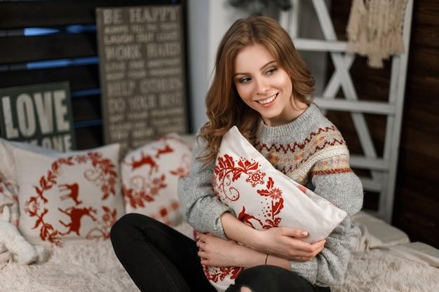 Giovane donna alla moda in un maglione lavorato a maglia alla moda con un cuscino si siede sul letto