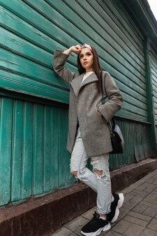 La giovane donna alla moda nell'abbigliamento giovanile alla moda primaverile della nuova collezione posa vicino all'edificio in legno verde in città. attraente ragazza elegante in abbigliamento casual con borsa nera alla moda sta riposando all'aperto.