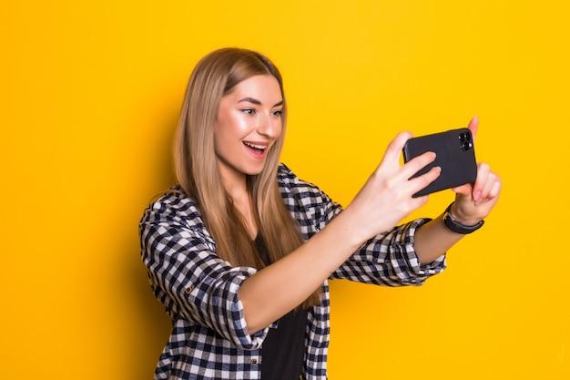 La giovane donna alla moda prende selfie sul telefono che posa sulla parete gialla,