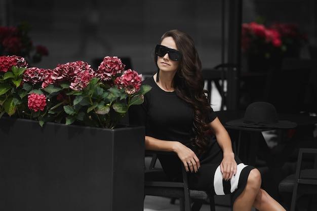 Una giovane donna alla moda in occhiali da sole alla moda e abito elegante seduto al tavolino del bar all'aperto