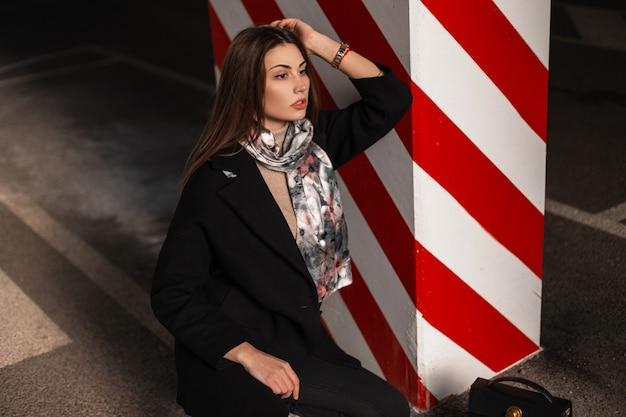 Giovane donna alla moda in vestiti eleganti della gioventù che posano nella città. modella sensuale ragazza in elegante cappotto nero con sciarpa primaverile di seta alla moda si rilassa vicino a una colonna con linea rosso-bianca all'aperto.