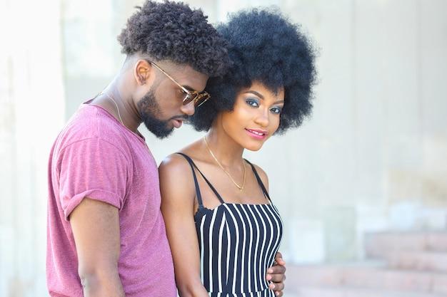 Giovane uomo e donna di colore vestiti alla moda