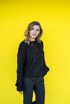 Ritratto alla moda di bella signora vicino al muro giallo. stile di vita