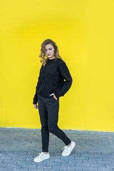 Ritratto alla moda di bella signora vicino alla parete gialla