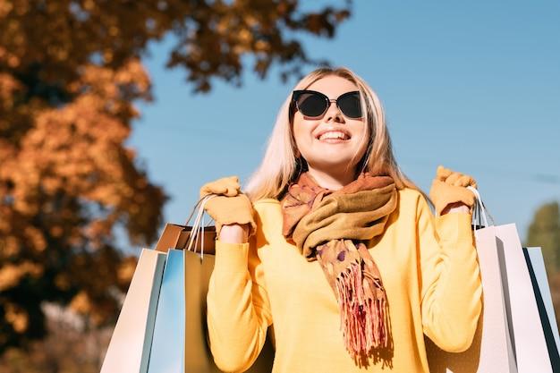Stile di vita fashionista. signora felice che cammina con le borse della spesa, godendo la giornata di sole autunnale.