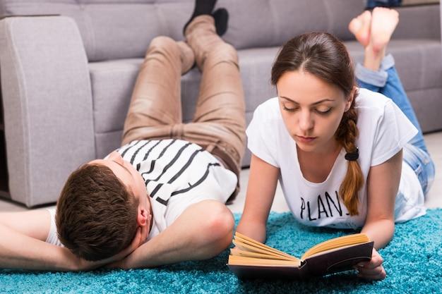 Fasion ragazza che legge un libro vicino al suo ragazzo sdraiato su un tappeto nel loro soggiorno in un'atmosfera rilassata