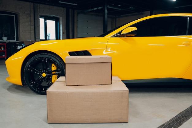 Concetto di consegna veloce. auto sportiva gialla e scatole.