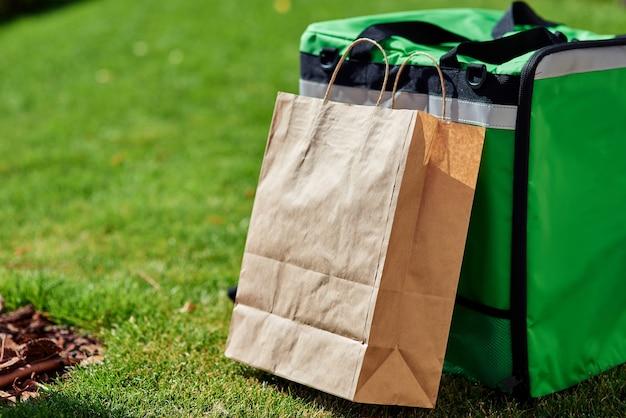 Zaino termico verde di consegna veloce e sacchetto di carta in piedi sull'erba verde all'aperto vicino