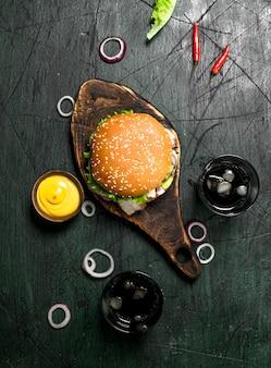 Fast food. hamburger con cola e salsa. su fondo rustico.
