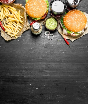 Fast food. hamburger con patatine fritte e cola. sulla lavagna nera.