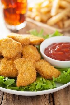 Pepite di pollo fast food con ketchup, patatine fritte, cola