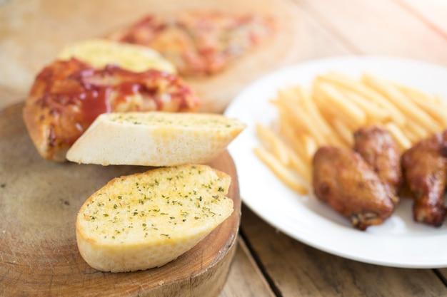 Fast food, ali di pollo croccanti, pane, patatine fritte e pizza su fondo di legno
