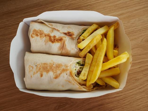 Fast food in una scatola per il pranzo di carta usa e getta su sfondo di legno vista dall'alto