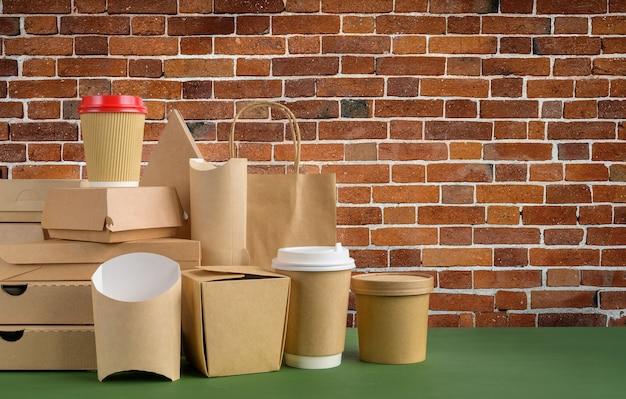 Pacchetto di fast food e bevande impostato sulla consegna di cibo di sfondo muro di mattoni