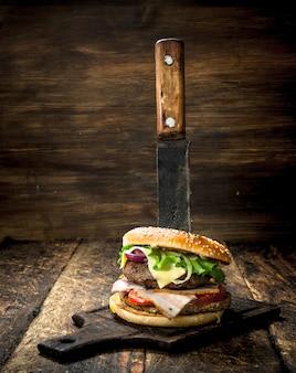 Fast food un hamburger fresco a base di carne di manzo e verdure con un grosso coltello su uno sfondo di legno