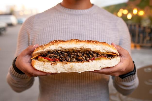 Fast food in mano. delizioso hot dog