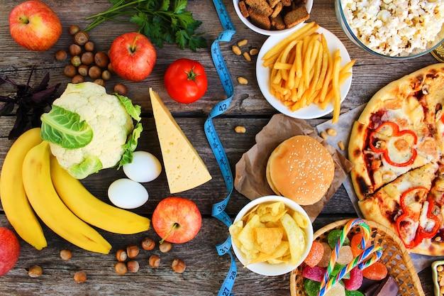 Fast food e cibo sano sulla vecchia tavola di legno. concetto che sceglie la corretta alimentazione o del cibo spazzatura. vista dall'alto.