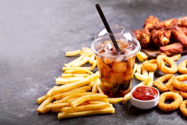 Pasti fast food: anelli di cipolla, patatine fritte, bicchiere di cola e pollo fritto sul tavolo scuro