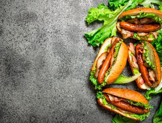 Menu fast food. barbecue di manzo hot dog con erbe baconnd sul tavolo rustico.