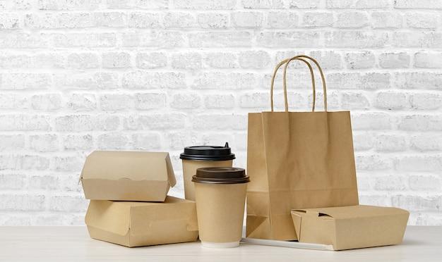 Set di imballaggi per fast food. tazze da caffè di carta, scatole per alimenti, sacchetto di carta marrone sul tavolo sullo sfondo del muro di mattoni bianchi