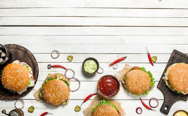 Fast food. vari hamburger con carne di manzo e verdure fresche. su un tavolo di legno bianco.