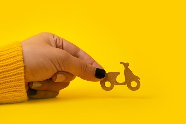 Consegna veloce e gratuita in scooter, scooter in legno in mano su sfondo giallo