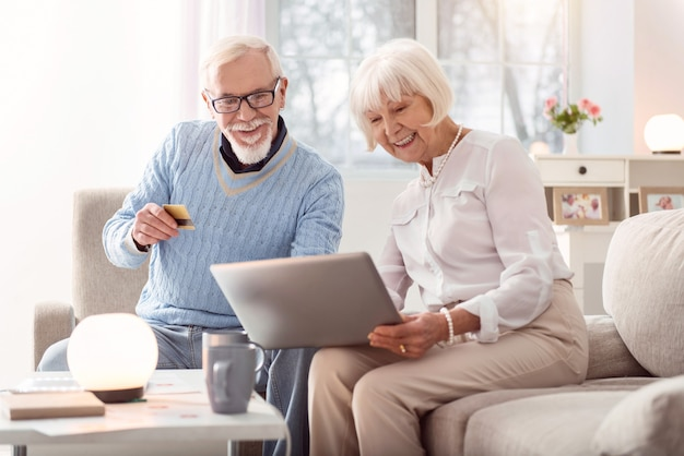 Pagamento veloce. allegro uomo anziano che consegna la sua carta di credito a sua moglie mentre guardano attraverso un negozio online e acquistano qualcosa