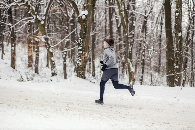 Corridore veloce che corre nella foresta il giorno di inverno nevoso. stile di vita sano, fitness invernale