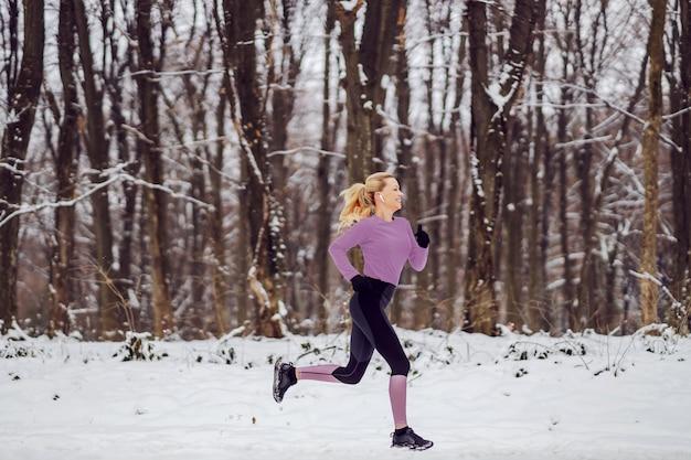 Sportiva veloce in abbigliamento sportivo caldo in esecuzione nei boschi nella neve nella natura in inverno. esercizi cardio, fitness invernale, clima freddo