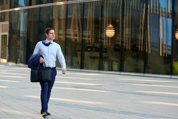 Uomo d'affari a piedi veloce che si affretta alla riunione durante la stagione calda