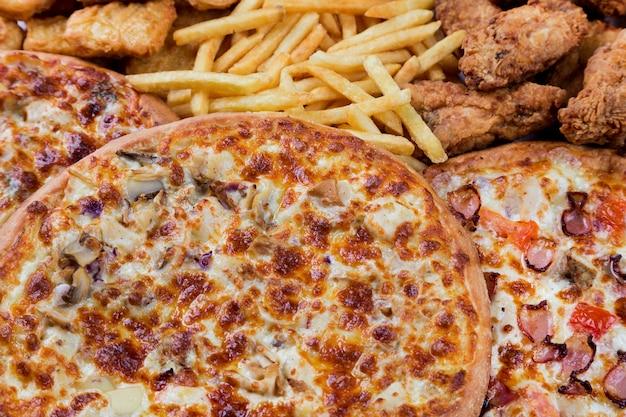 Bocconcini di pollo fast food, cosce, pizze e patate fritte