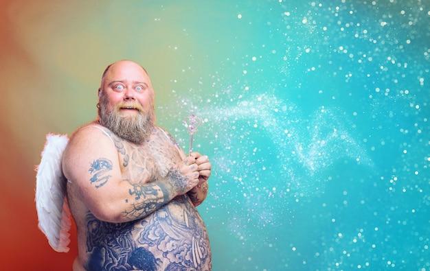 L'uomo grasso e stupito con barba tatuaggi e ali si comporta come una fata magica