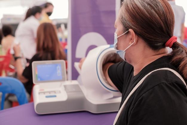 La donna anziana grassa dell'asia ha inserito la sua mano nell'assistenza sanitaria del monitor della pressione sanguigna e nel controllo medico