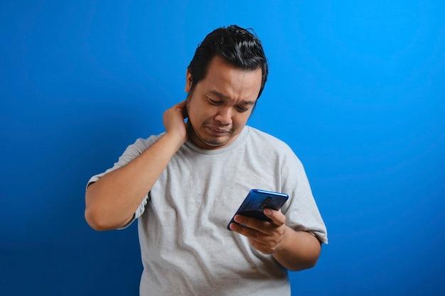 Un ragazzo asiatico grasso che indossa una maglietta grigia sembra triste leggendo le notizie online dal suo cellulare. l'uomo mostra un gesto deluso asciugandosi le lacrime dal viso
