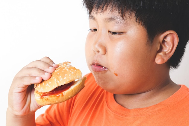 I bambini asiatici grassi mangiano hamburger. concetti alimentari che causano problemi di salute fisica dei bambini.