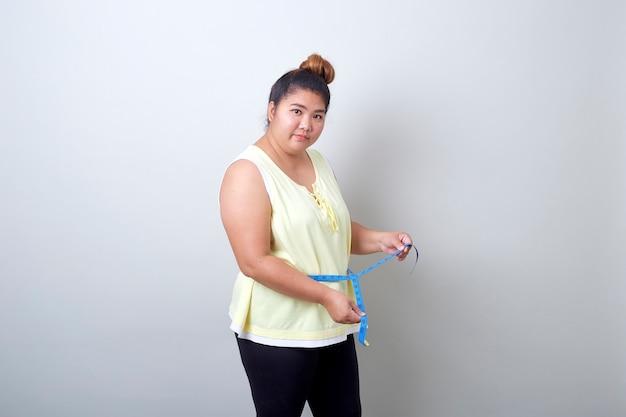 Donna asiatica grassa che misura
