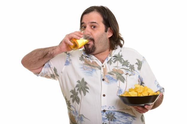 Uomo caucasico barbuto grasso che beve birra e che tiene ciotola di patatine fritte pronte per le vacanze
