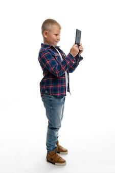 Lo scolaro grasso del ragazzo esamina la compressa. a tutta altezza. muro bianco. insegnamento a distanza. verticale.