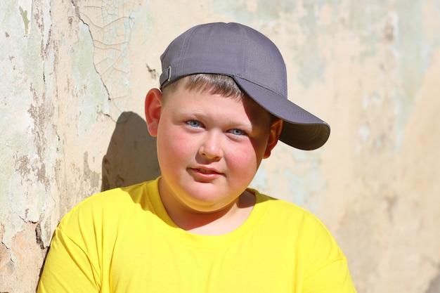 Un ragazzo grasso con una maglietta gialla e un berretto blu sta contro il muro in estate. foto di alta qualità