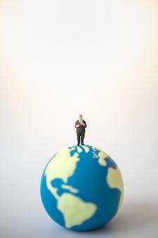Persone in miniatura di grasso uomo d'affari in piedi sulla mini sfera del mondo.