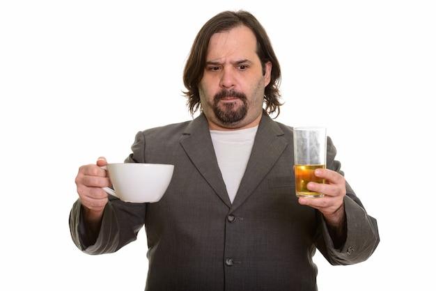 Uomo d'affari caucasico grasso che sceglie tra caffè e birra isolato su bianco