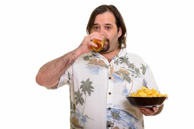 Uomo caucasico grasso che beve birra e che tiene ciotola di patatine fritte pronte per le vacanze