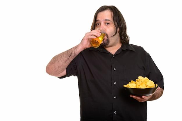Uomo caucasico grasso che beve birra mentre si tiene una ciotola di patatine isolato su bianco