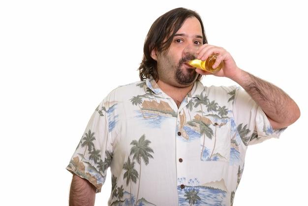 Uomo caucasico grasso che beve un bicchiere di birra isolato su bianco