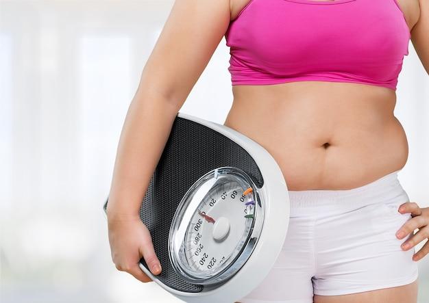Pancia femminile grassa e squama sullo sfondo