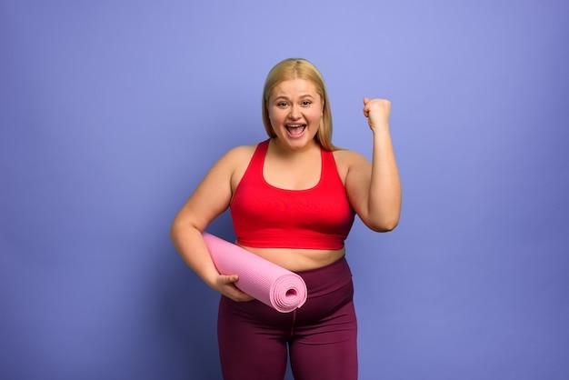 Ragazza grassa fa palestra a casa soddisfatta e con successo espressione sfondo viola