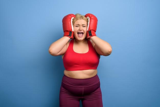 La ragazza grassa è preoccupata perché non può perdere peso. sfondo viola