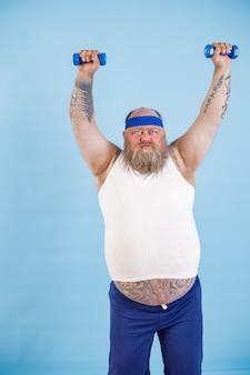 L'uomo grasso fa esercizi sportivi con manubri cercando di perdere peso su sfondo azzurro
