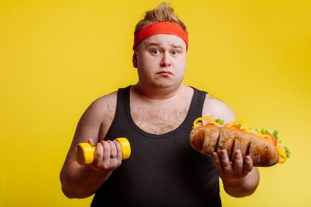 Uomo grasso e tenendo hamburger e manubri