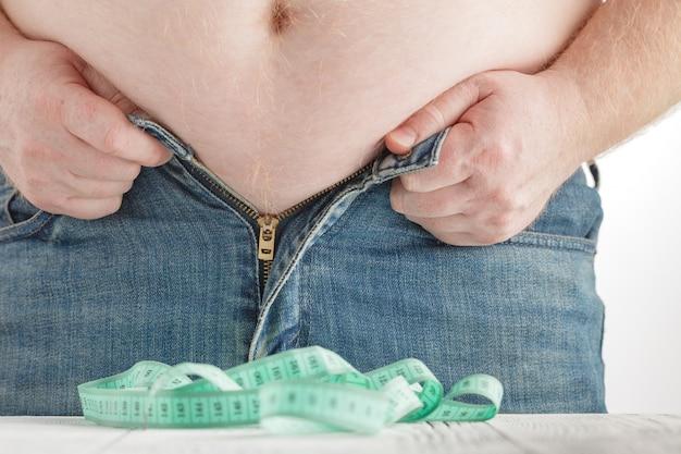 Uomo grasso che tiene un nastro di misurazione. perdita di peso.